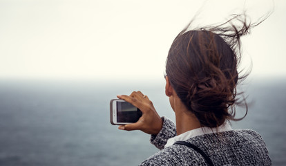 Beautiful young woman taking photos and selfies with her smartphone of the ocean with wind going through her long hair.