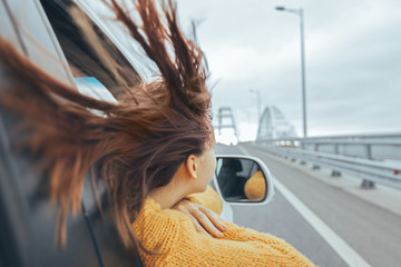 Girl in car looking forward on a bridge at weekend road trip