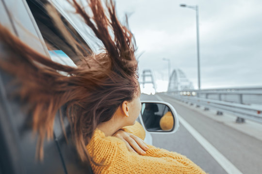 Girl in car looking forward on a bridge at weekend road trip