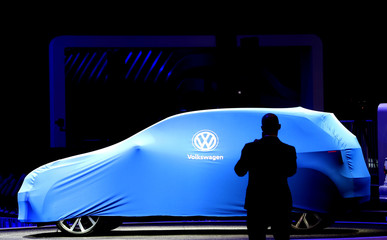 A person takes a photograph of an unrevealed Volkswagen car during the first media day of the  Salao do Automovel International Auto Show in Sao Paulo