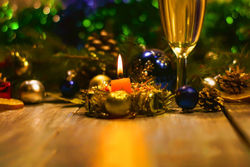 candle and a glass of champagne or white wine on a new year background. Christmas and New Year decorations