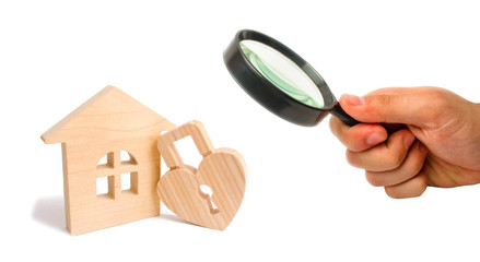 Magnifying glass is looking at the Wooden house with Heart shaped lock on a white background. Love nest, relationships. Buying a house with a young family. Affordable housing. Family psychology