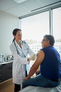 Doctor giving male patient a shot in the arm