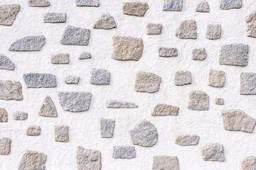 Eine weiße Wand mit großen und kleinen Steinen als Hintergrund