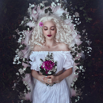 Sleeping beauty. Enchanted Princess lies in a coffin in flowers with a bouquet. Sleeping in the dark woods.
