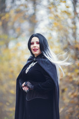 Portrait of vampire woman in black cloak with amulet