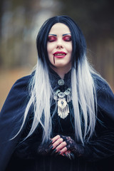 Photo of gothic vampire girl with eyes closed with blood at mouth