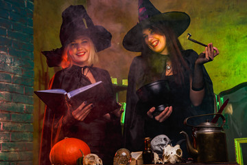 Portrait of smiling witches in black hats with book and magic cauldron at table with pumpkin and skulls