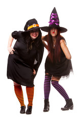 Full-length photo of two cheerful witches in hats and striped socks