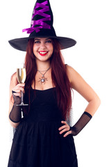 Photo of laughing witch in black hat, with glass of champagne