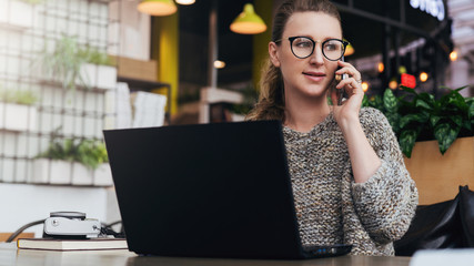 Young woman sitting in office, cafe at table in front of laptop and talking on mobile phone. Freelancer works in a cafe.
