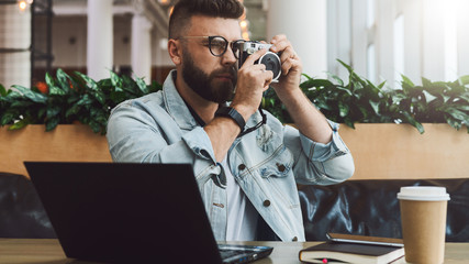 Young bearded man in denim jacket sits in coffee shop at table in front of laptop and takes instant photo on camera.