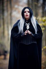 Photo of vampire girl in black cloak on blurred background