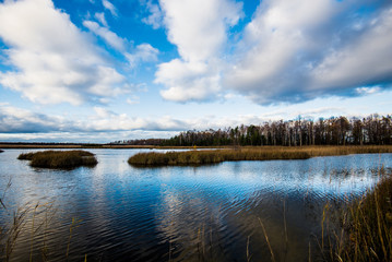 An autumn landscape. A view of the river against cloudy blue sky, Latvia