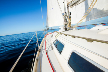 White yacht sails in the Baltic sea on a sunny day. A view from the deck to the bow and sails. Latvia