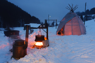 Old stove with tipi tent and alpine copper cheese making pot in the snow.