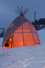 Tipi tent glowing from inside fire in the evening in snowy environment.