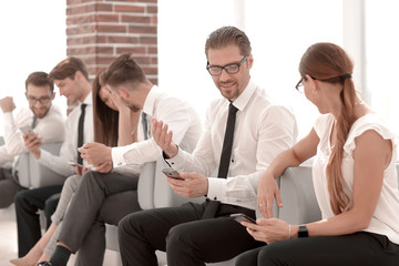 employees of the company using their smartphones sitting in the office lobby