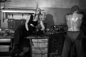 Man and a beautiful woman in a metalwork shop.