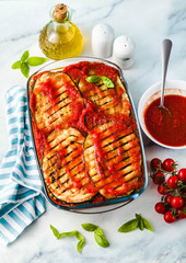 Vegan Eggplant Parmigiana made of peas and lentils and fresh tomatoes on a marble kitchen table. Healthy comfort recipe for the whole family