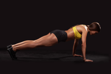 young muscular woman doing fitness exercise plank isolated on black background