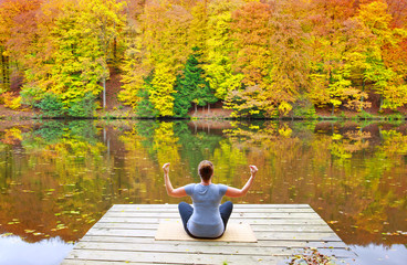 Woman meditating outdoors in the autumn park near forest lake.