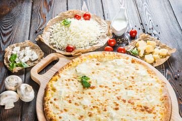 Big cheese pizza on a round cutting board on a dark wooden background. Pizza ingredients