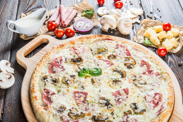 Creamy pizza with ham and mushrooms on a round cutting board on a dark wooden background. Pizza Ingredients. Macro