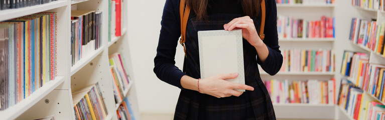Female hands holding a book in shop on background of bookshelves. Girl choosing what to read in bookstore.