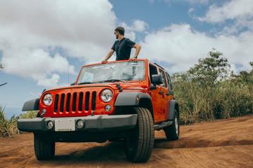 Young man standing inside a hawaiian convertible car