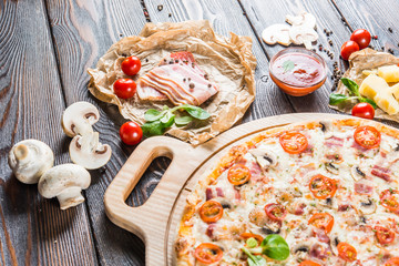 Big pizza with bacon, mushrooms and tomatoes on a round cutting board on a dark wooden background. Food Ingredients. Macro