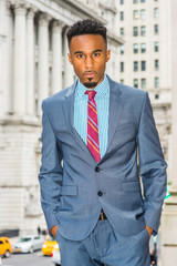 Portrait of Young African American Businessman with beard in New York, wearing dark sky blue suit, white patterned shirt, violet red patterned tie, standing on street by old office building, looking..