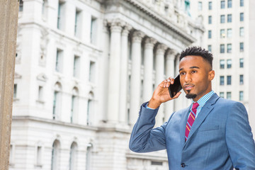 Young African American Businessman with beard working in New York, wearing dark sky blue suit, violet red patterned tie, standing on street outside vintage office building, talking on cell phone..