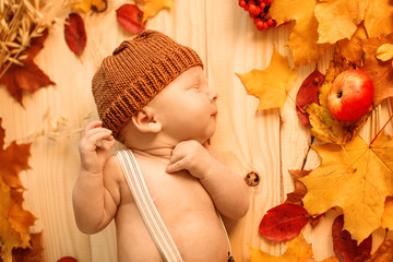 Autumn newborn. Autumn time scene. little  baby with red yellow maple leaves, berries, pumpkin, apples, harvest.