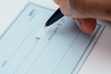 writing a check with blue pen on white background Wall mural