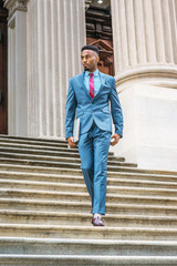 Young African American Businessman with beard working in New York, wearing sky blue suit, violet red patterned tie, dark purple leather shoes, holding laptop computer, walking down stairs from office