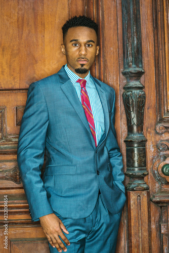 315d4037a4 Portrait of Young African American Businessman with beard in New York,  wearing gray blue suit, white patterned shirt, purple patterned tie, ...