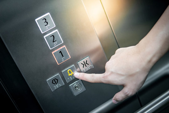 Male forefinger pressing on emergency stop and alarm button in elevator (lift). Mechanical engineering concept