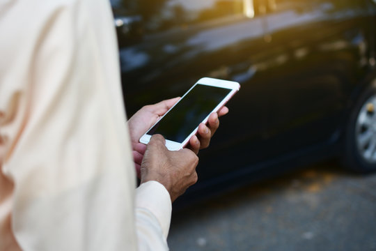 Businessman holding smart phone and standing at car
