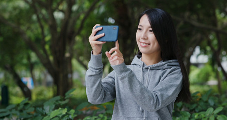 Woman take photo on cellphone in park