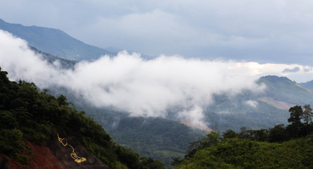 View of the mountains with fog above green hills.