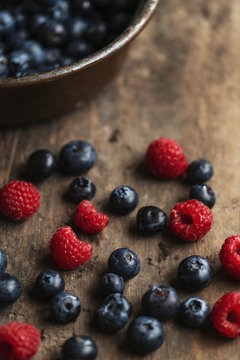 Fresh strawberries and blueberries on a wooden table