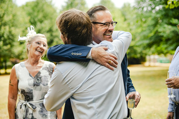 Fathers of the bride and groom hugging it out