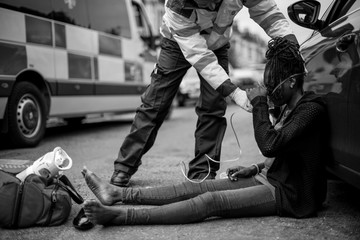Male paramedic putting on an oxygen mask to an injured woman on a road