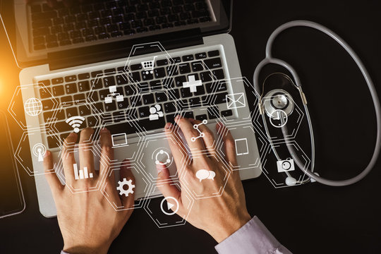 Medical doctor hand working with smart phone,digital tablet computer,stethoscope on black desk,virtual icons screen. top view