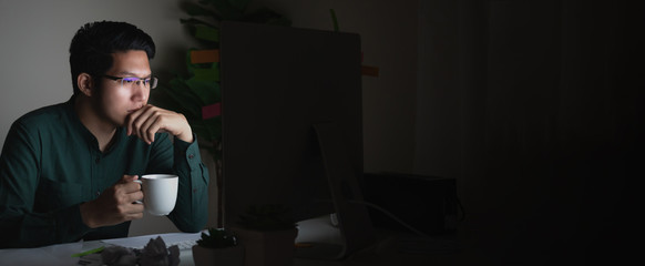 Banner of attractive young asian man drinking coffee sitting on desk table looking at laptop computer in dark late night working feeling serious thinking and determinated at home office concept.
