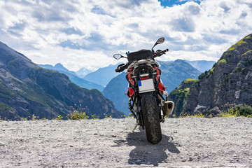 Back view of a motorbike parked on top of the mountain road, high rocky mountains in the background. Adventure, freedom and independence. Summer outdoor activity