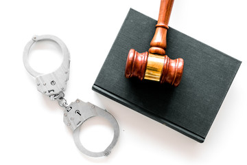 Crime concept. Metal handcuffs near judge gavel and law book on white background top view