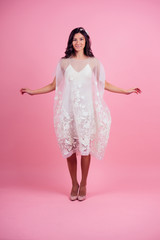 young woman with curly hair wearing white dress on a pink background in the studio. girl jumping for joy