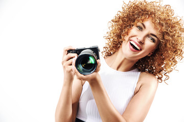 Cheerful frizzy-haired lady holding a digital camera